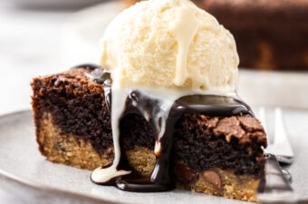 A slice of brookie pie on a grey plate with chocolate sauce oozing down the sides and a scoop of ice cream on top