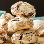 A stack of 3 chocolate meringues on a sheet of brown baking paper