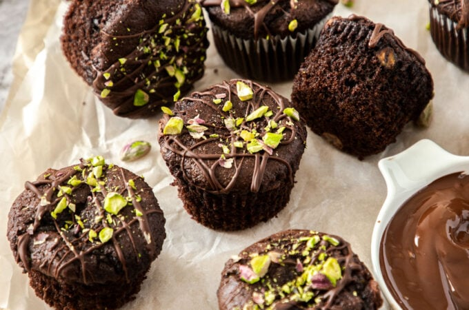 A batch of chocolate muffins on a sheet of baking paper with pistachios scattered on top and around