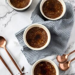 4 chocolate creme brulees on a marble table with bronze coloured spoons next to them
