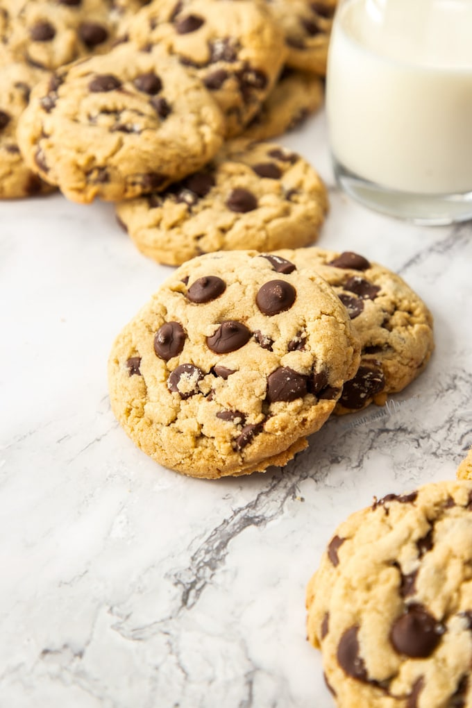 Closeup of a pile of chocolate chip cookies on a marble bench top