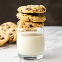 A stack of 3 chocolate chip cookies on top of a glass of milk