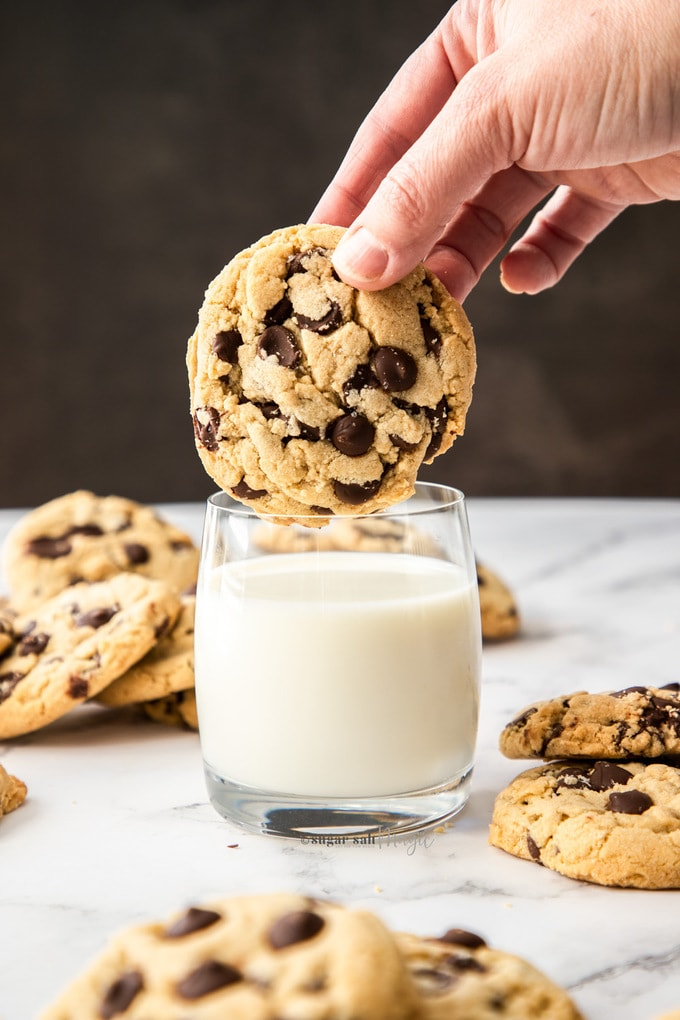 A large chocolate chip cookie being dunked into a glass of milk with more cookies sitting around it