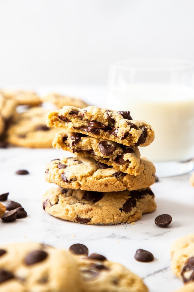 A stack of chocolate chip cookies with the top one broken in half revealing gooey choc chips