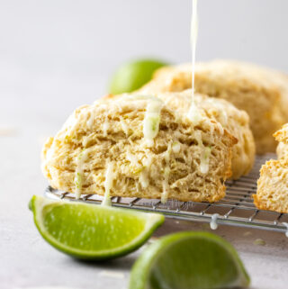 Closeup of a scone on a wire rack with icing being drizzled on top
