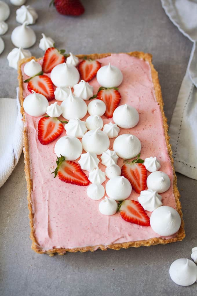 Strawberry Mousse Tart decorated with meringues and sliced strawberries.