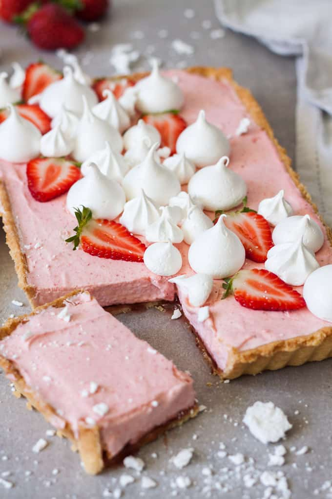 A Strawberry Mousse Tart with a corner cut out of it.
