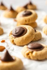 Closeup of a peanut butter thumbprint cookie leaning against another one. More are in the background and foreground