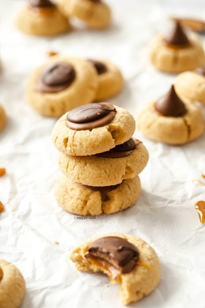 A stack of 3 caramel peanut butter thumbprint cookies on a sheet of baking paper with more around.