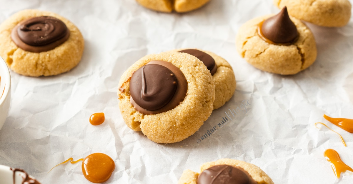 A batch of caramel peanut butter thumbprint cookies on a sheet of baking paper
