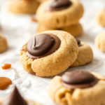 A peanut butter thumbprint cookie leaning against another one with more surrounding them