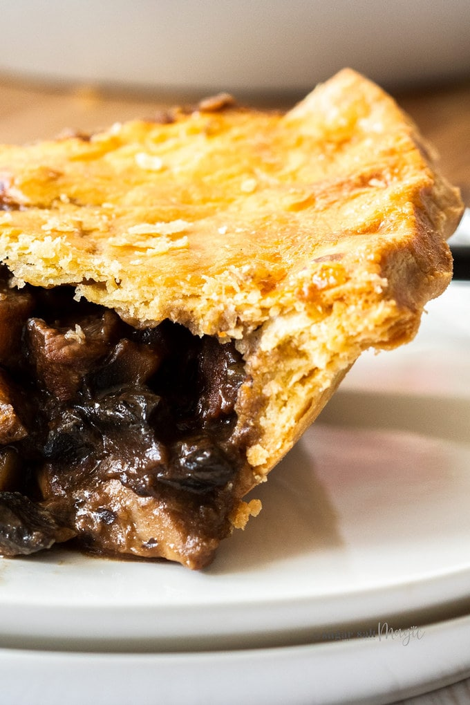 Closeup of the side of a slice of beef pie showing the flaky texture.