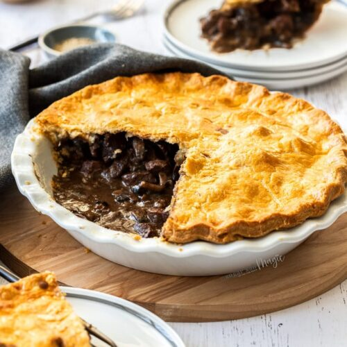 Beef pie in a white pie dish showing the inside. It sits on a wooden board.