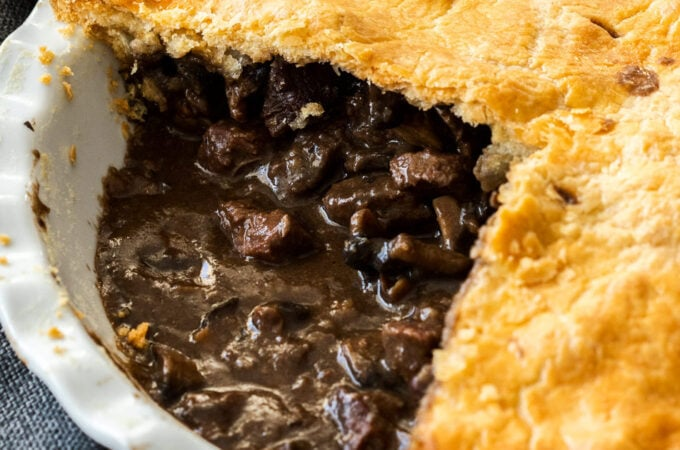 Closeup of the in meat filling in a pie in a white pie dish. It sits on a wooden board
