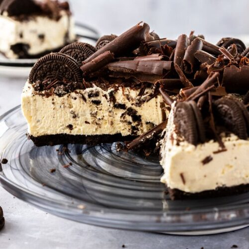 An oreo cheesecake with 2 slices cut out, showing the inside of the cake. It sits on a black glass plate with oreos and crumbs strewn around it.