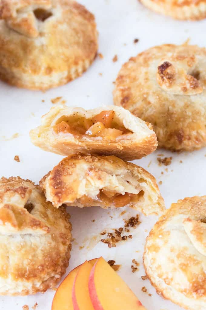 These Spiced Peach Hand Pies are a combination of fresh peaches, a kick of cinnamon and ginger, all wrapped up in the perfect buttery pie crust. These mini pies are the perfect portable dessert.