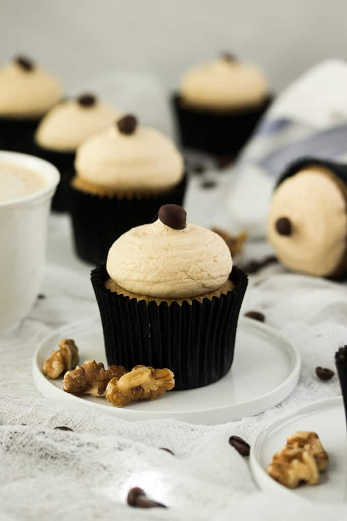 A Walnut Coffee Cupcake on a small plate with walnuts by the side