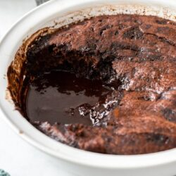 Chocolate pudding with sauce in a white pie dish