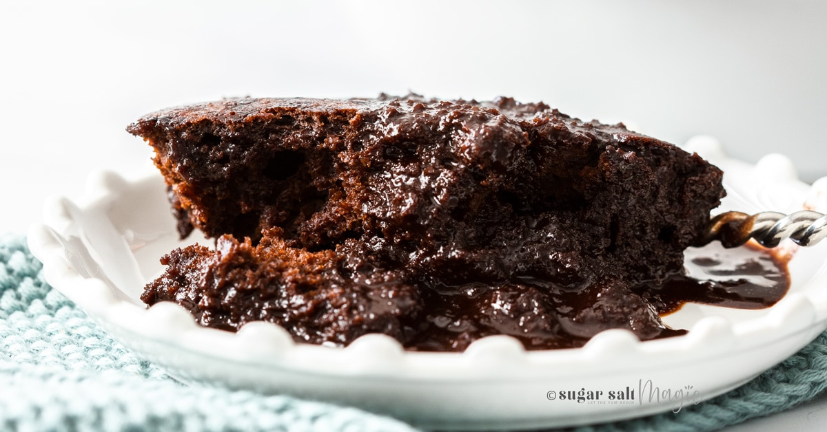 A piece of chocolate self saucing pudding on a white plate with a turquoise serviette