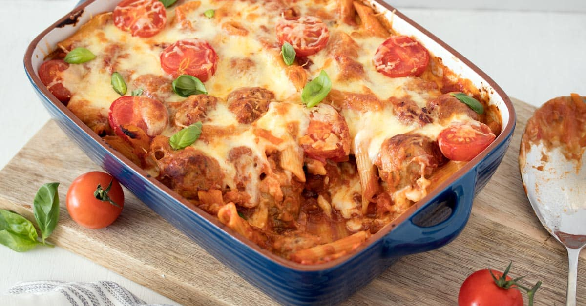 In the mood for a comforting Meatball Pasta Bake Recipe? Easy beef and pork meatballs in a simple tomato sauce, tossed with penne pasta and baked to gooey perfection.