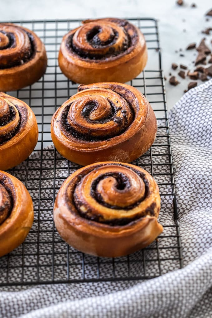 3 chocolate filled cinnamon rolls lined up on a wire rack with a tea towel underneath