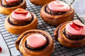 6 cinnamon rolls with pink icing on a wire rack with a tea towel underneath. Chocolate pieces scattered around.