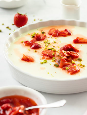 A large white dish filled with panna cotta. Some macerated strawberries sit on top and in front.