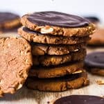 A stack of dark brown sugar cookies on a white wooden board.