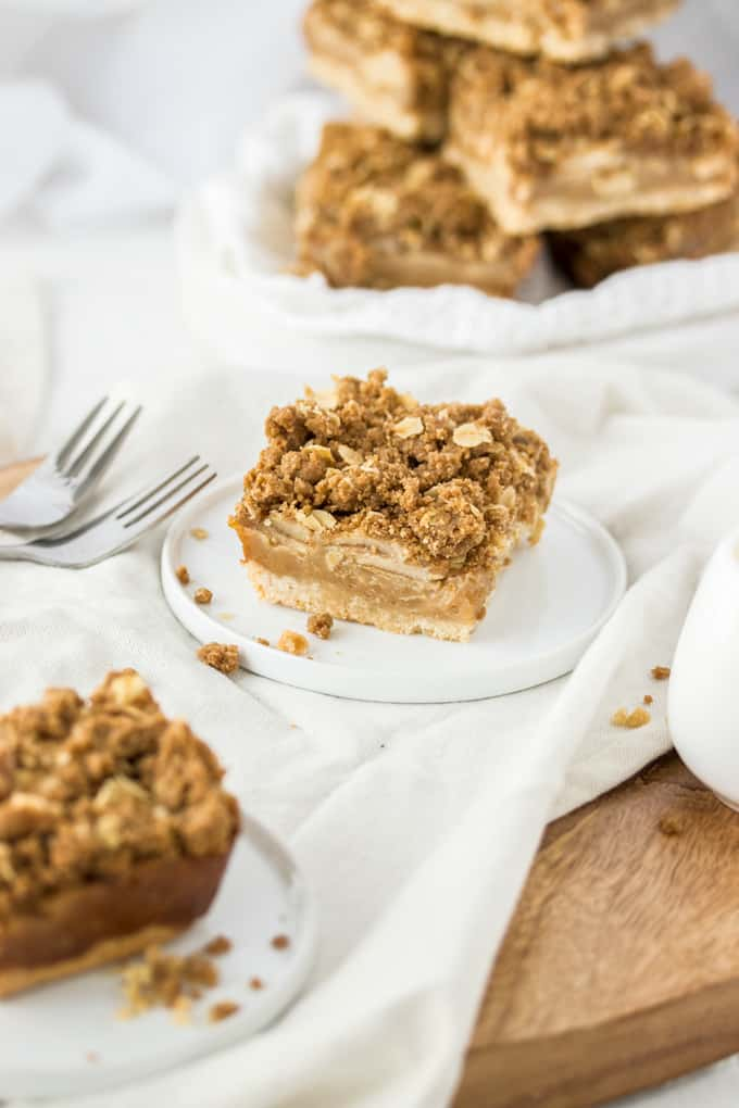 A caramel apple pie bar on a white plate with more stacked in the background