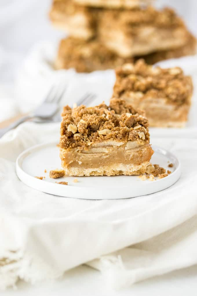 A Caramel Apple Pie Bar showing layers of shortbread base, caramel apple filling and crumble topping on a white plate on a white napkin.
