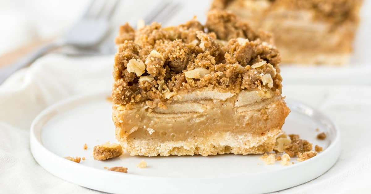 A Caramel apple pie bar on a white plate with 2 forks in the background