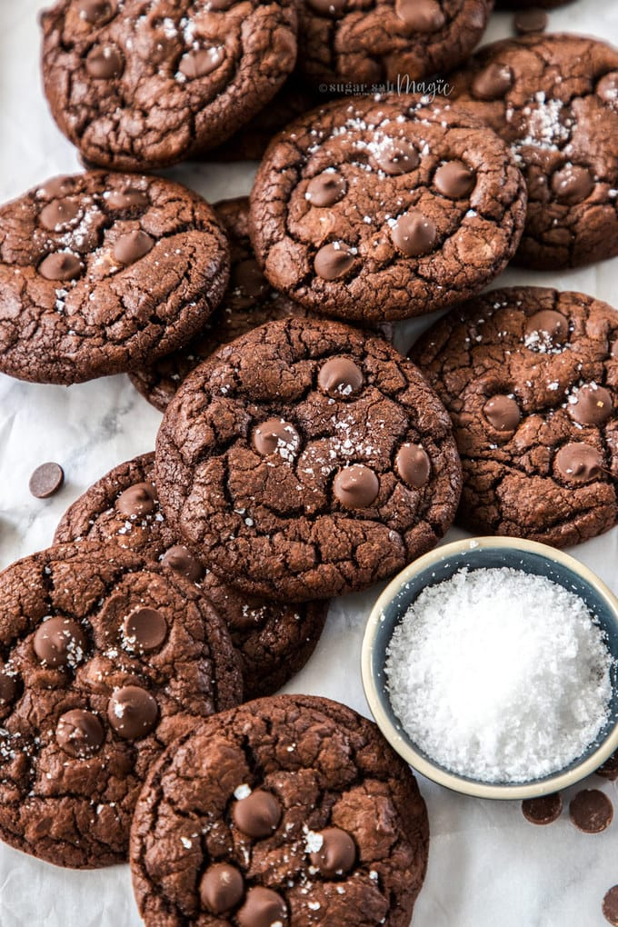 A batch of chocolate cookies piled next to a small dish of salt flakes