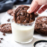 A chocolate cookie being dunked into a glass of milk with more cookies scattered around it