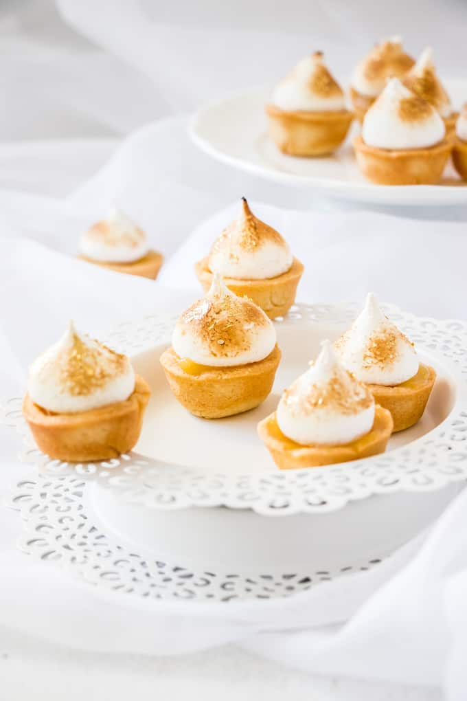 Mini Lemon Meringue Pies sitting on white plates.