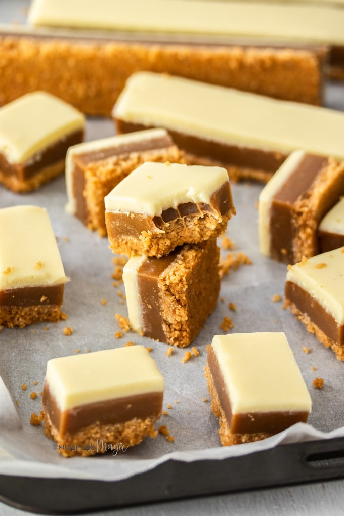 squares of caramel slice covered in white chocolate on a sheet of baking paper. one with a bite taken out