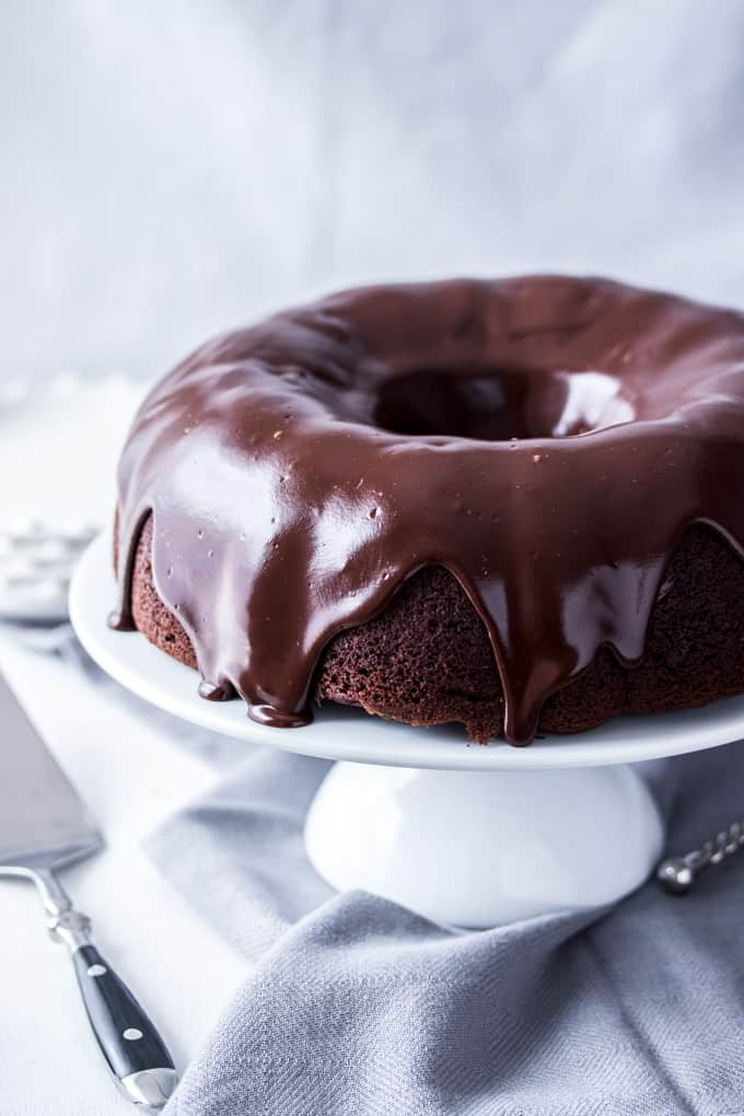 A Chocolate Bundt Cake covered in chocolate ganache on a white cake stand.
