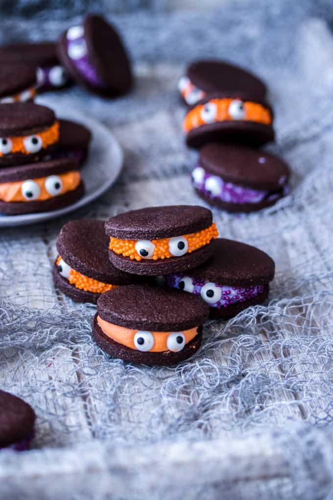A pile of 4 Chocolate Monster Halloween Cookies with more in the back and on a plate.