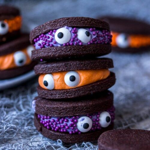 A stack of 3 chocolate cookies with candy eyes stuck to them.