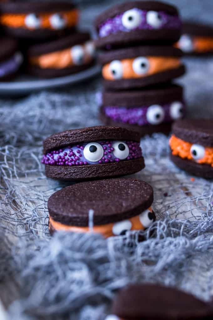 Chocolate sandwich cookies with purple and orange filling, decorated with sprinkles and eye balls.