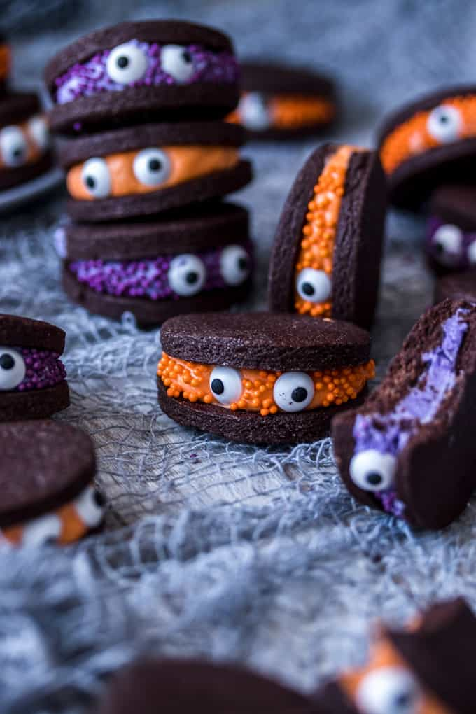 Piles of chocolate sandwich cookies decorated with eye balls to look like cute little monsters.