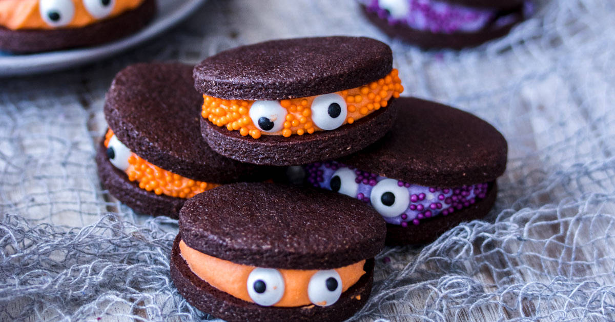 A pile of 4 chocolate sandwich cookies with orange and purple filling.