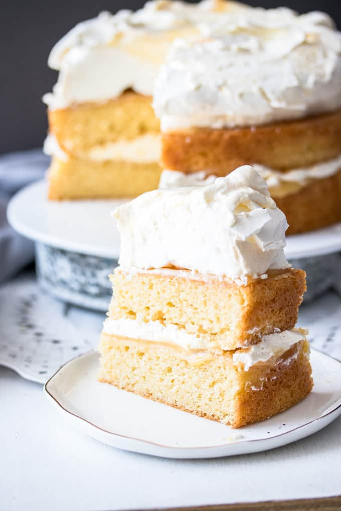 A slice of 2-layer Lemon Meringue Cake on a white plate, the whole cake is in the background.