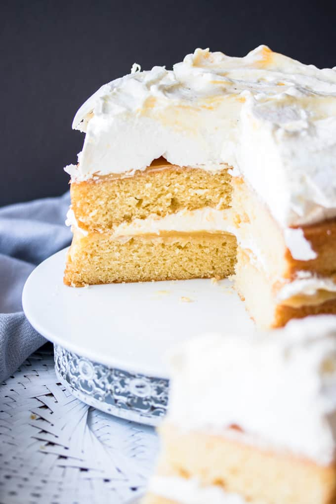 A Lemon Meringue Cake with slices cut off showing in the inside.