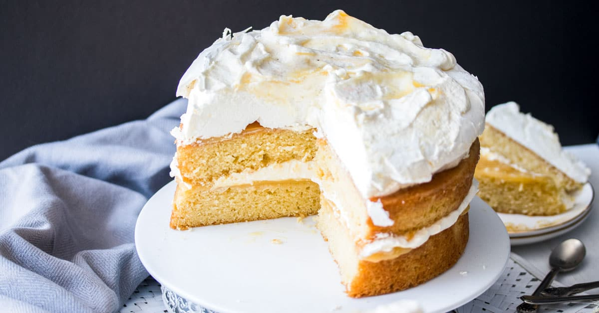 A Lemon Meringue Cake with a quarter of it cut off, sitting on a cake stand.