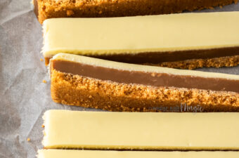 Rows of caramel peanut butter slice on a sheet of baking paper