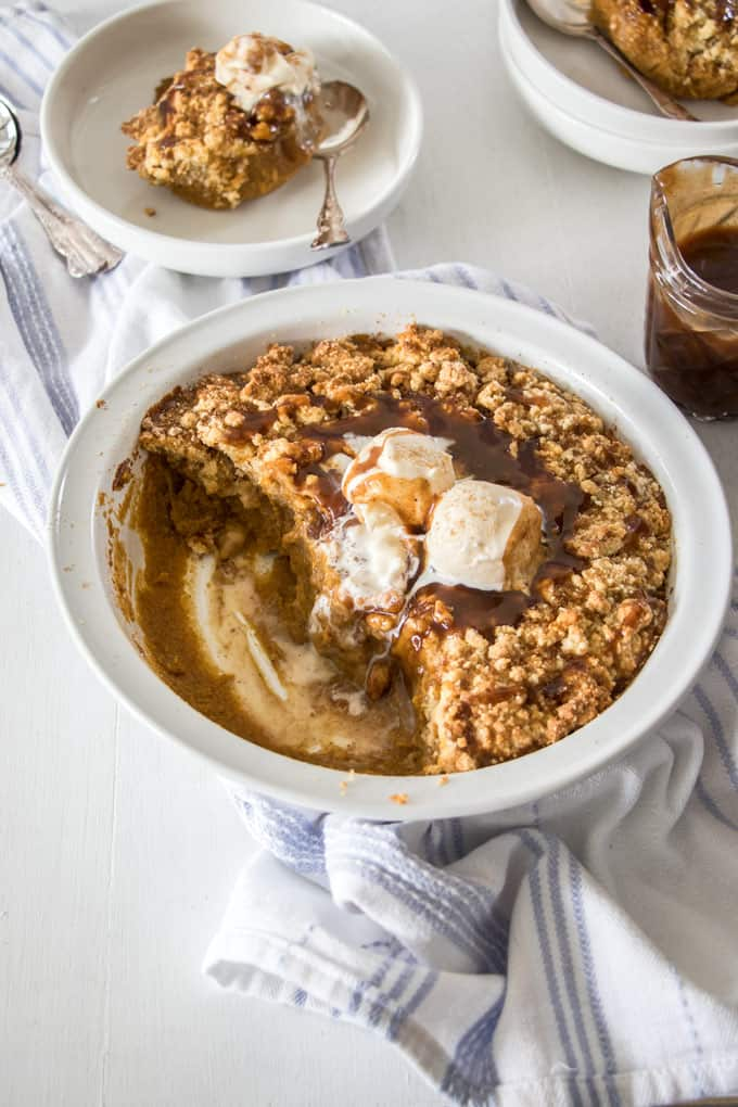 Pumpkin cobbler in a white pie dish, a single serving is on a small white dish in the back.