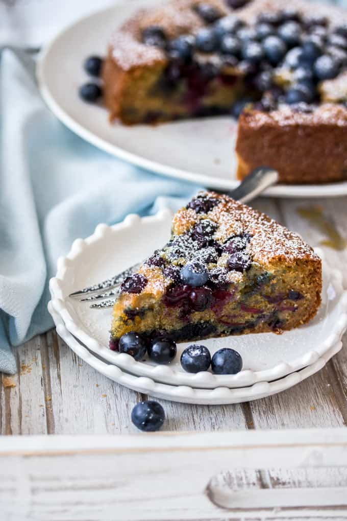 A slice of blueberry cake on a small white plate with blueberries around