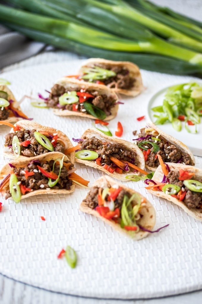 A group of mini Korean tacos on a white mat with a bunch of spring onions in the background