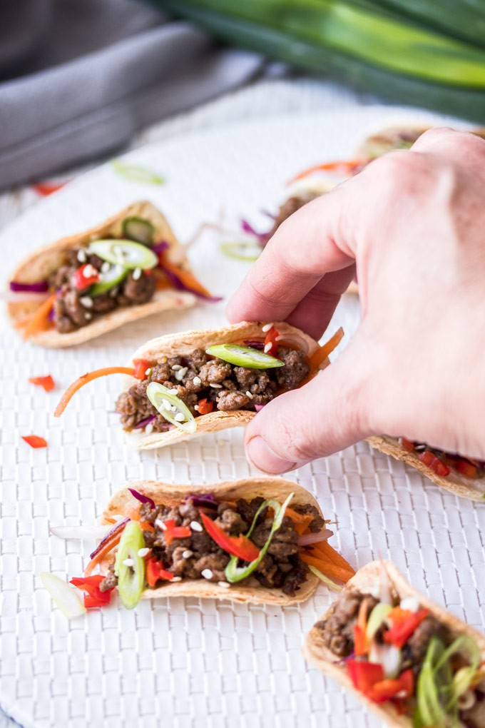 A hand reaching, picking up a mini korean beef taco off a white mat with others around it and green onions in the background
