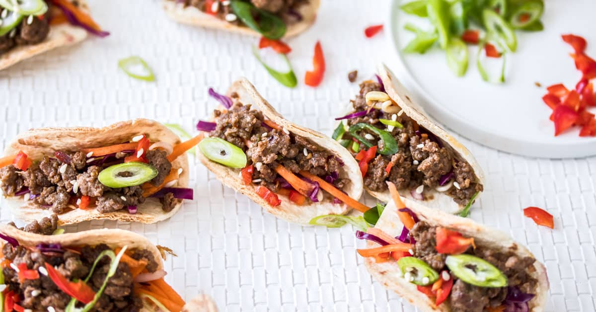 Closeup of 7 mini Korean beef tacos on a white mat